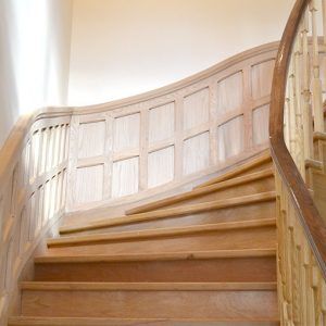 Solid oak curved staircase with oak panelling